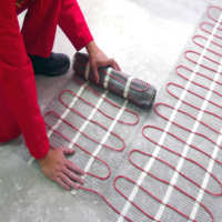 Self regulating electric underfloor heating engineer installing.png