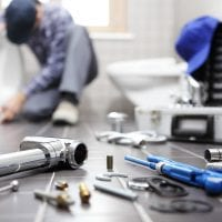 plumber-at-work-in-a-bathroom-plumbing-repair-service-assemble-109779262.jpg